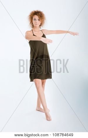 Full length portrait of a young woman in dress and curly hair dancing isolated on a white background