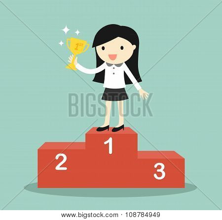 Business concept, business woman standing on the winning podium and holding trophy.