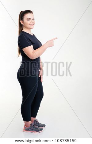Full length portrait of a sports fat woman pointing finger away isolated on a white background