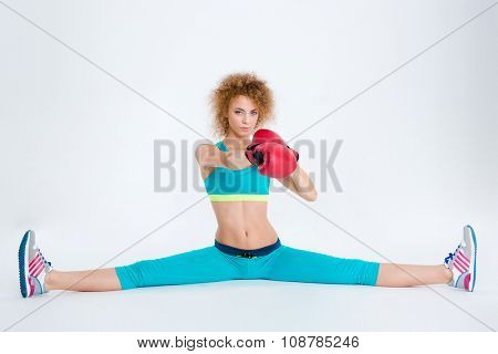 Portrait of attractive woman with curly hair doing twine and boxing in red gloves isolated on a white backgorund
