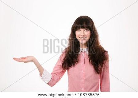 Portrait of a happy woman holding copyspace on the palm isolated on a white background