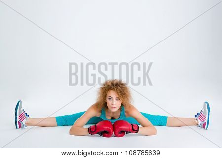 Portrait of a beautiful sports woman in boxing gloves doing twine isolated on a white backgorund