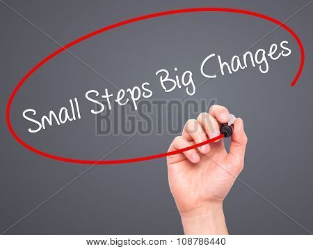 Man Hand writing Small Steps Big Changes with black marker on visual screen.