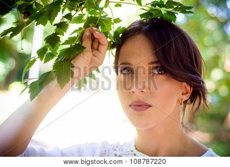 Thoughtful Woman Holding Green Leaves Of A Tree