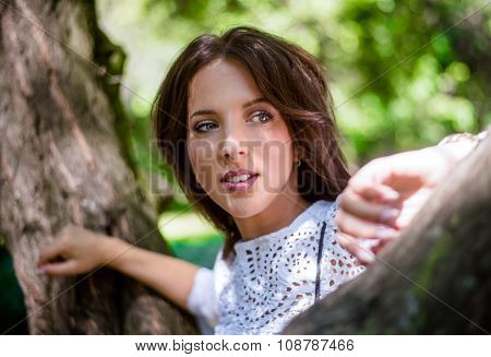 Thoughtful Woman Leaning Against Tree Trunk