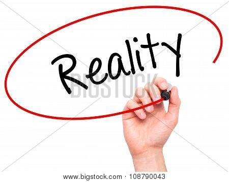 Man Hand writing Reality with black marker on visual screen.