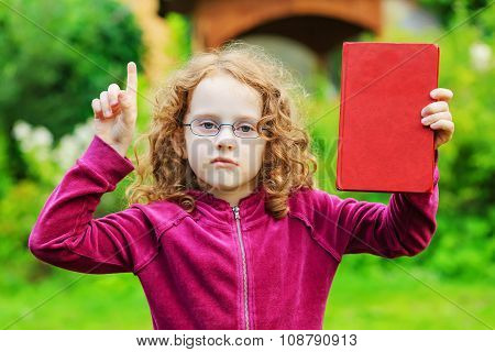 Little Girl In Eyeglasses With Red Book And Finger Up.
