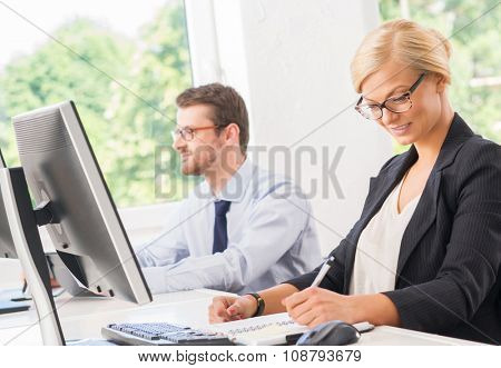 Beautiful female boss making an appointment in her notebook.