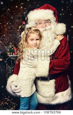 Santa Claus holds on hands happy little girl. Christmas scene.