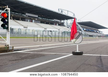 motosports, extreme and race concept - close up of red traffic lights and road sign with flag on speedway track or road