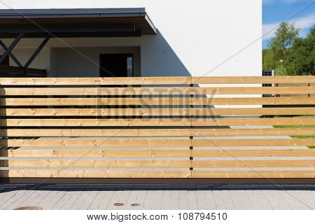 security, real estate and home concept - close up of rail fence in front of private living  house