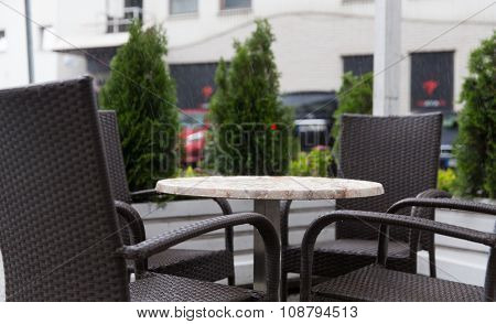 weather, public places and season concept - table and wicker chairs on street cafe terrace under rain