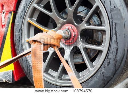 motosports, transportation and racing concept - close up of race car wheel with tow rope tied to it