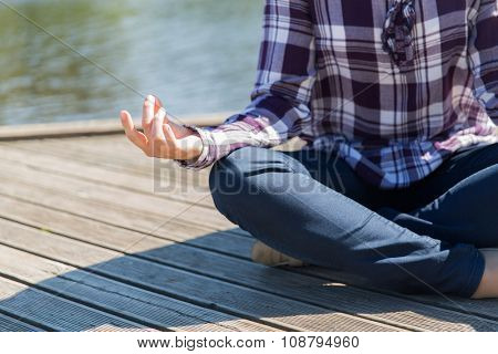 yoga, meditation, people and lifestyle concept - close up of woman meditating in lotus pose outdoors on berth