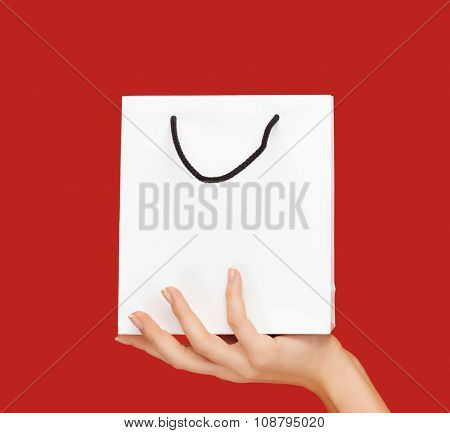 people, sale, consumerism, advertisement and commerce concept - close up of hand holding blank white bag over red background