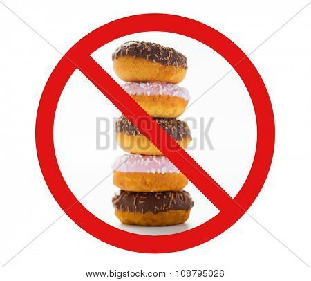 fast food, low carb diet, fattening and unhealthy eating concept - close up of glazed donuts pile over white behind no symbol or circle-backslash prohibition sign