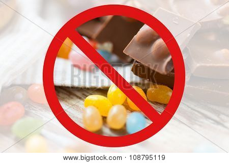 low carb diet, fattening and unhealthy eating concept - close up of jelly beans candies and chocolate behind no symbol or circle-backslash prohibition sign