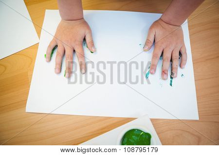 Boy pressing his paint covered hands in a sheet of paper