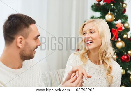 love, christmas, couple, proposal and people concept - happy man giving diamond engagement ring to woman at home