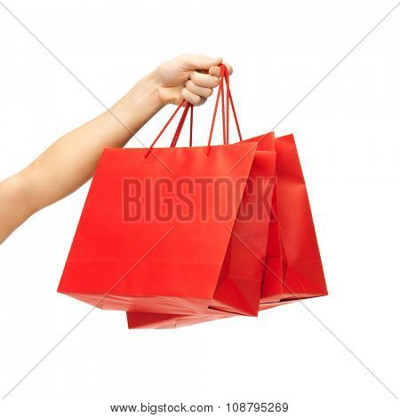 people, sale, consumerism, advertisement and commerce concept - close up of hand holding red blank shopping bags
