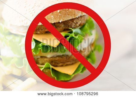 fast food, low carb diet, fattening and unhealthy eating concept - close up of hamburger or cheeseburger behind no symbol or circle-backslash prohibition sign