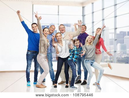family, gender, generation and people concept - group of happy men, women and boy having fun and waving hands over empty office room or home