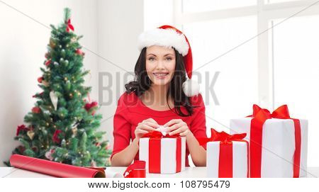 holidays, celebration, decoration and people concept - smiling woman in santa helper hat with decorating paper packing gift boxes over living room and christmas tree background
