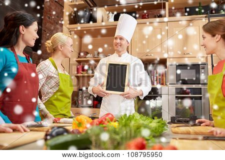 cooking class, culinary, food and people concept - happy women and chef cook with blank menu chalk board in kitchen over snow effect