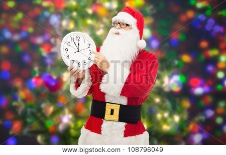 christmas, holidays, time and people concept - man in costume of santa claus with clock showing twelve over party lights background