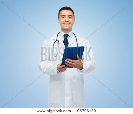 healthcare, profession, people and medicine concept - smiling male doctor in white coat with tablet pc over blue background