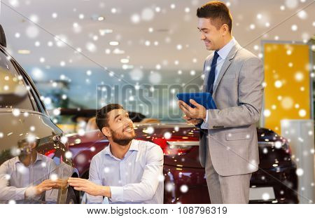 auto business, car sale, technology and people concept - happy man and car dealer with tablet pc computer talking in auto show or salon over snow effect