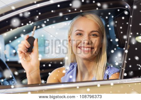 auto business, car sale, consumerism and people concept - happy woman taking car key from dealer in auto show or salon over snow effect
