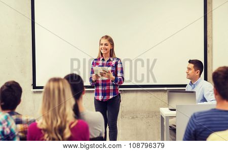 education, high school, technology and people concept - smiling student girl with tablet pc, laptop computer standing in front of classmates and teacher in classroom