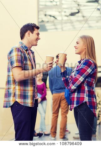 friendship, people, drinks and education concept - group of smiling students with paper coffee cups outdoors