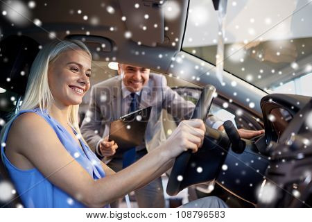 auto business, car sale, consumerism and people concept - happy woman with car dealer in auto show or salon over snow effect