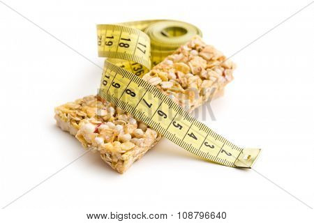 muesli bar and measuring tape on white background