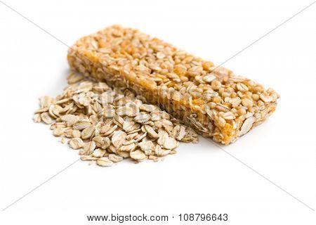 muesli bar and oat flakes on white background