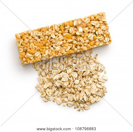 muesli bar and oat flakes on white background