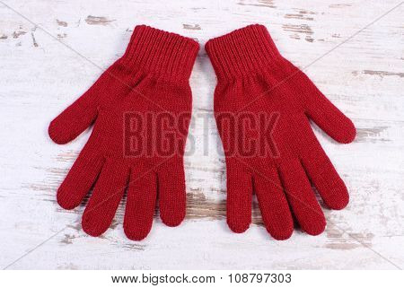 Pair Of Woolen Gloves For Woman On Old Wooden Background