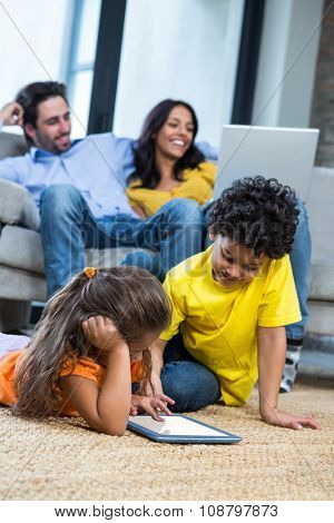 Children laying on the carpet using tablet in living room while parents on sofa using laptop