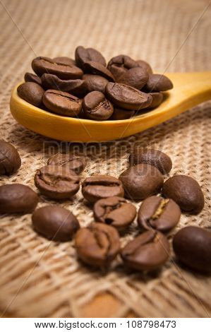 Heap Of Coffee Beans With Wooden Spoon On Jute Canvas