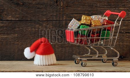 trolley with Santa hat over wooden background