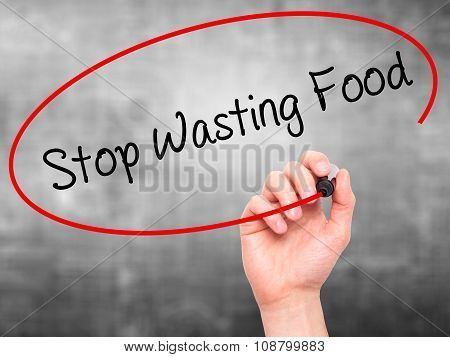 Man Hand writing Stop Wasting Food with black marker on visual screen.