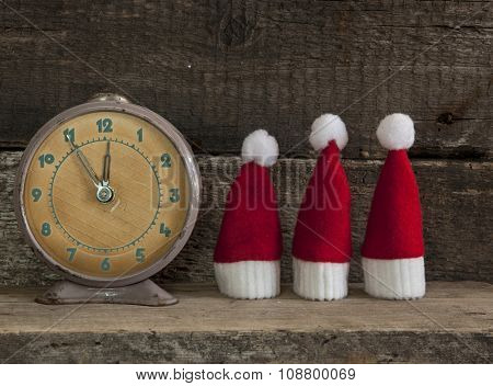 vintage alarm clock and christmas decoration on wooden background