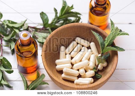 Pills  In Bowl, Leaves Of Mint, Essential Aroma Oil On White Table.