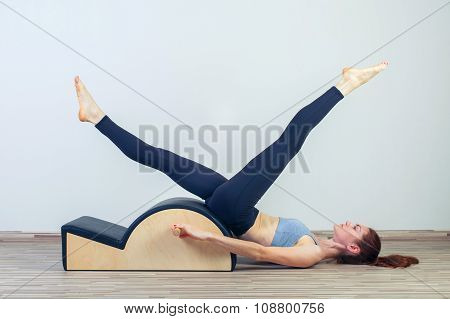Pilates, fitness, sport, training and people concept -  woman doing  exercises on small barrel