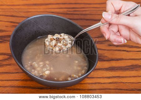 Hand Holds Tablespoon With Beans Soup Over Bowl