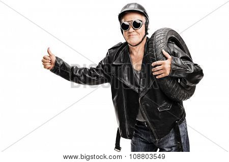 Senior biker in a black leather jacket carrying a tire and hitchhiking with his thumb isolated on white background