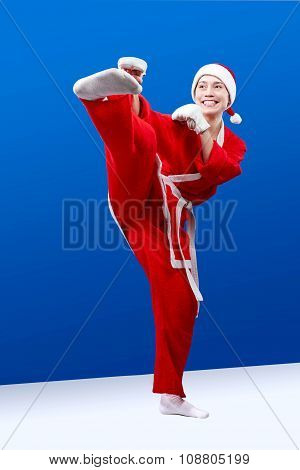 A girl dressed as Santa Claus doing karate kick