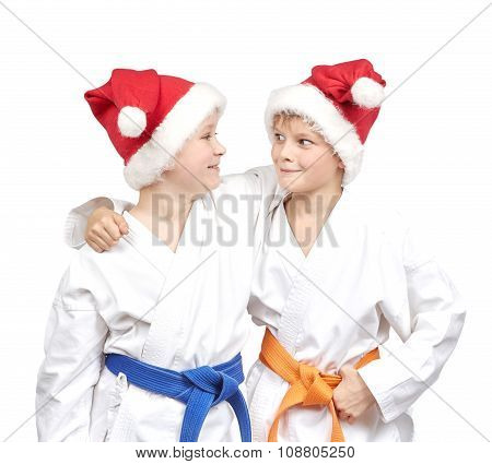 Two boys embrace in a kimono and wearing Santa hat